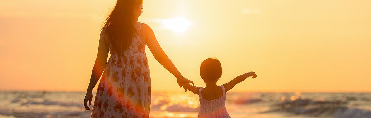海辺で手をつなぐ母親と子供
