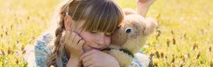 クマのぬいぐるみを抱きしめる少女